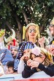 LIMASSOL, CHIPRE - 26 DE FEBRERO: Carnivalists en sombreros de un cilindro de la plata alegre sigue la banda del municipio de Lim Fotografía de archivo