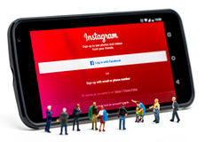 LIMASSOL, CYPRUS - DECEMBER 07, 2015: Group of people watching at Instagram application sign. In page on smartphone. Social networking concept on December 7 stock image