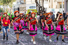 LIMASSOL, CYPRUS - FEBRUARY 26: Carnivalists in a silver cylinder hats joyfully follow the Limassol Municipality Band Royalty Free Stock Images