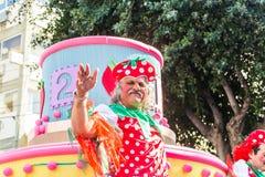 LIMASSOL, CYPRUS - FEBRUARY 26: Carnivalists in a silver cylinder hats joyfully follow the Limassol Municipality Band Royalty Free Stock Photography