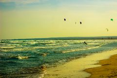 Limassol, Cyprus - 12, 03, 2018: Gliding up and down with their surf boards Kite Surfing on the coastal waves of Cyprus royalty free stock photo