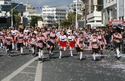 Children in carnival costumes running along a street royalty free stock photography