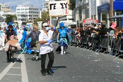 People in carnival costumes marching along a street royalty free stock image