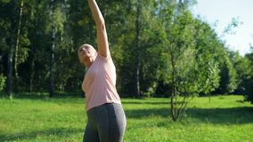 Senior nice woman doing warm up exercises outdoors stock footage