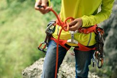 Сlimber wearing safety harness making a eight rope knot. Women climber wearing safety harness making a eight rope knot Royalty Free Stock Photos