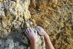 Сlimbers hands. A climbers hands searching for grippy holds on a narrowish crack running up a crag Stock Photography