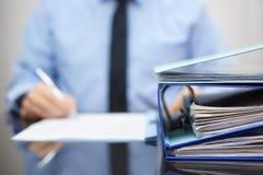 Limbindningar med legitimationshandlingar väntar för att bearbetas med affärsmannen Arkivfoto