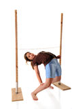 Limbo. A preteen girl bending backwards under a limbo stick.  Isolated on white Royalty Free Stock Image