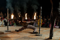 Limbo dance under the fire. A performer of the Asante Kenya Acrobats dances an extreme limbo in front of enthusiast children during the Milan Clown Festival Royalty Free Stock Photo