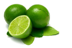 Lime. Two whole limes, one half lime, with leaves,  on white Royalty Free Stock Photo