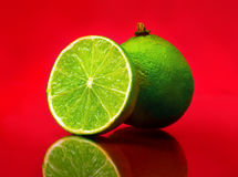 Lime. Isolated on red background Stock Photos