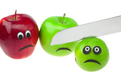 Lime and apple with eyes and faces and knife Stock Photos