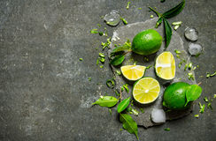 Lime background. Slices of lime with ice and leaves on a stone stand . Royalty Free Stock Photography