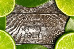 Lime backgrounds. Slice of lime with leaves on a piece of wood Royalty Free Stock Images