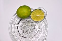 Lime citrus, whole and cut on glass juicer Royalty Free Stock Photos
