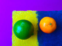 Lime and clementine on colored background Stock Image