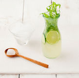Lime cucumber lemonade cocktail on a white table Stock Photos