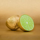 Lime cut with golden peel on gold background Stock Photo