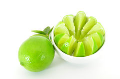Lime with cut lime in bowl. And leaves isolated on white Stock Image