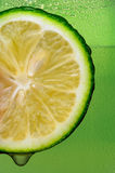 Lime with drip and Green Background Royalty Free Stock Photos