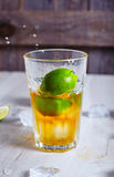Lime that dropped into glass with rum and ice Stock Photos