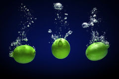 Lime dropped into water Stock Photography