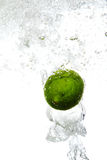 Lime is dropped into water Stock Images