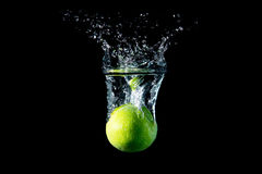 Lime drops in water Royalty Free Stock Photos