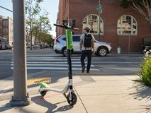 Lime electric scooter resting at an intersection in San Francisco, CA royalty free stock image