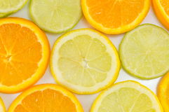 Lime fruit and orange slices making background. Pattern Royalty Free Stock Photos