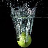 Lime Fruit Splash. A lime fruit splashing into water against black background Stock Photos