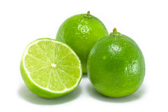 Lime fruits. Two and a half lime citrus fruits, one bisected, isolated on a white background Stock Image