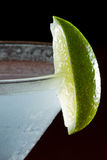Lime garnish. Lime wedge on the rim of a martini glass used as a garnish isolated on a black background stock photos