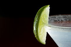 Lime garnish. Lime wedge on the rim of a martini glass used as a garnish isolated on a black background royalty free stock photos