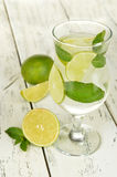 Lime into glass of water on white wooden background Stock Photos