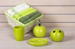 Lime green bath accessories with towels basket on wooden background Royalty Free Stock Photo