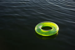 Lime green inflatable ring floating on dark water royalty free stock photography