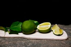 Lime and green leaves on a wooden chopping board. A Picture of Lime and green leaves on a wooden chopping board Stock Images