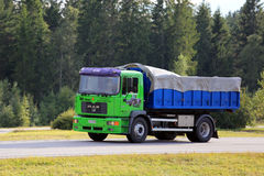 Lime Green MAN 18. 284 Truck on Motorway. PAIMIO, FINLAND - AUGUST 19, 2016: Lime green MAN 18. 284 tipper truck moves along motorway in against green forest stock photo