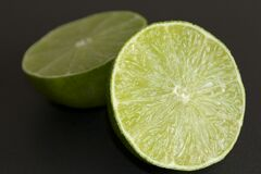 Lime halves on black background Stock Photos