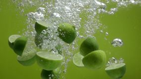 Lime halves falling into water stock video footage