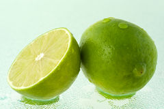 Lime and its half with water drops. A whole green lime and a half, covered by drops of water, on wet glass surface Stock Image