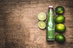 Lime juice in bottle with fresh lime fruits on rustic wooden background, top view Royalty Free Stock Images