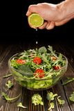 Lime juice is squeezed into a dish with salad Royalty Free Stock Photos