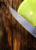 Lime and knife. On wooden board. Royalty Free Stock Image