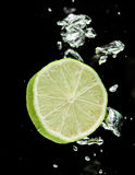 Lime (lemon) falling in water Royalty Free Stock Photography