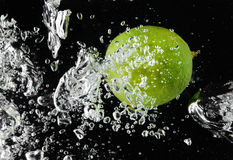 Lime (lemon)  falling in water on black Royalty Free Stock Images