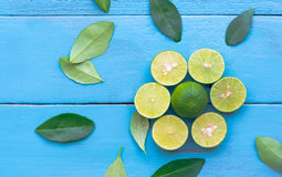 a Lime lemon are half cut on blue wooden background. Leadership Stock Photo