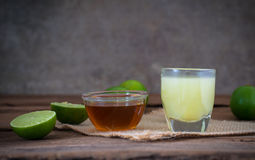 A Lime lemon with juice  and honey in transparent glass with sac Royalty Free Stock Photography