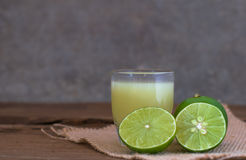 A Lime lemon and juice in transparent glass with sack cloth on r Royalty Free Stock Images
